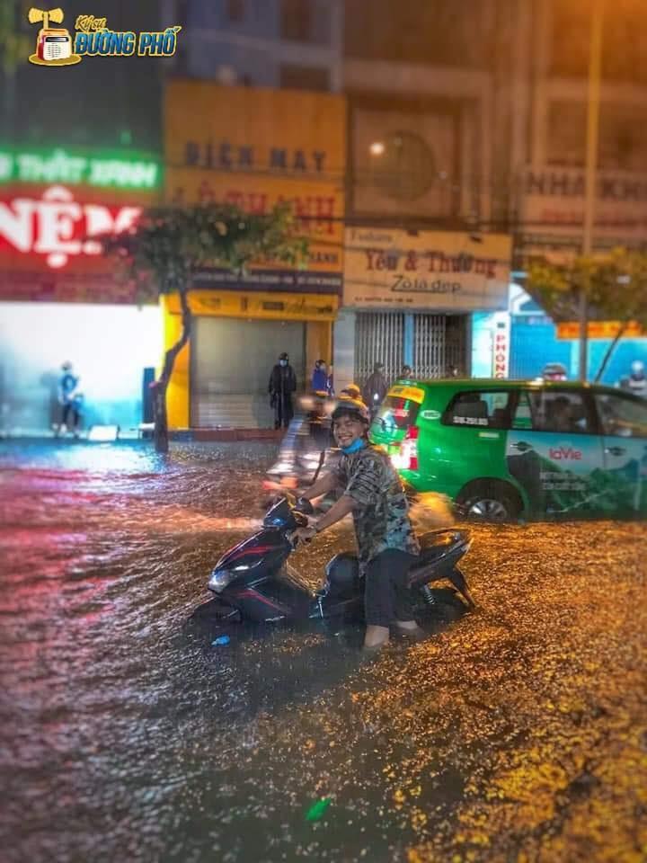 Nụ cười của một thanh niên dắt xe máy trên đường ngập