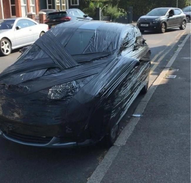 Chiếc ô tô đỗ chắn lối đi và bị bọc giấy bóng kính quanh xe