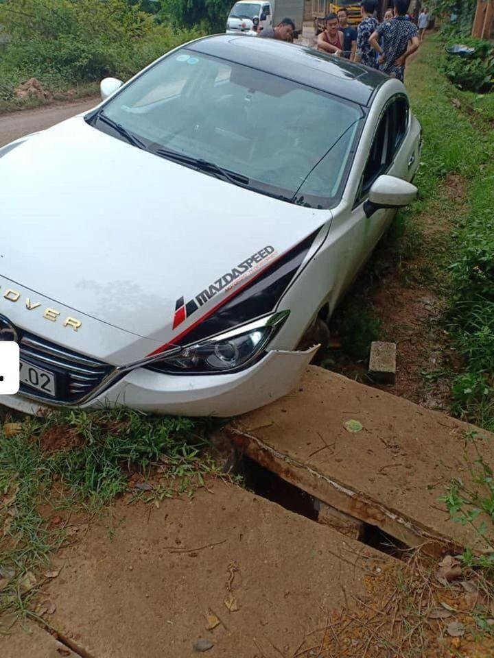 Chiếc ô tô Mazda tông trúng lối đi vào nhà dân, bắc qua rãnh thoát nước