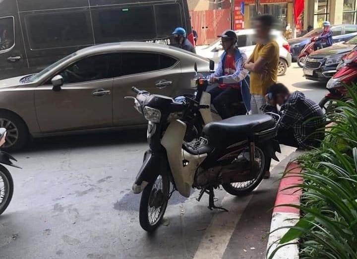 Nam thanh niên ngồi bên đường và ôm mặt, chiếc xe máy cũng bị hư hỏng