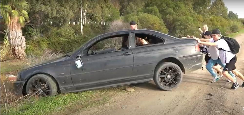 Taylor và bạn bè cùng nhau đẩy chiếc BMW 3-Series xấu số xuống bờ sông