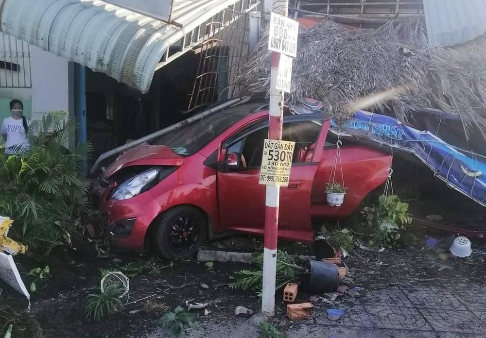 Chiếc xe Chevrolet Spark hư hỏng đầu xe, quán cà phê bên đường và mái hiên nhà dân hư hỏng nặng