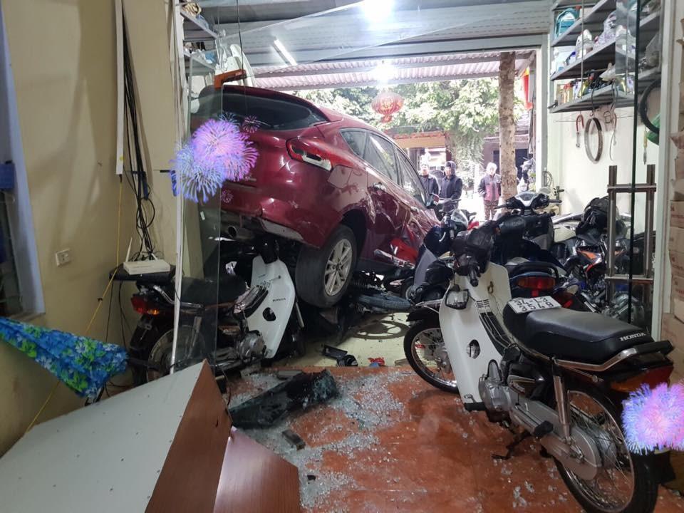 Chiếc ô tô Ford Focus nằm đè lên một vài chiếc xe máy trong cửa hàng