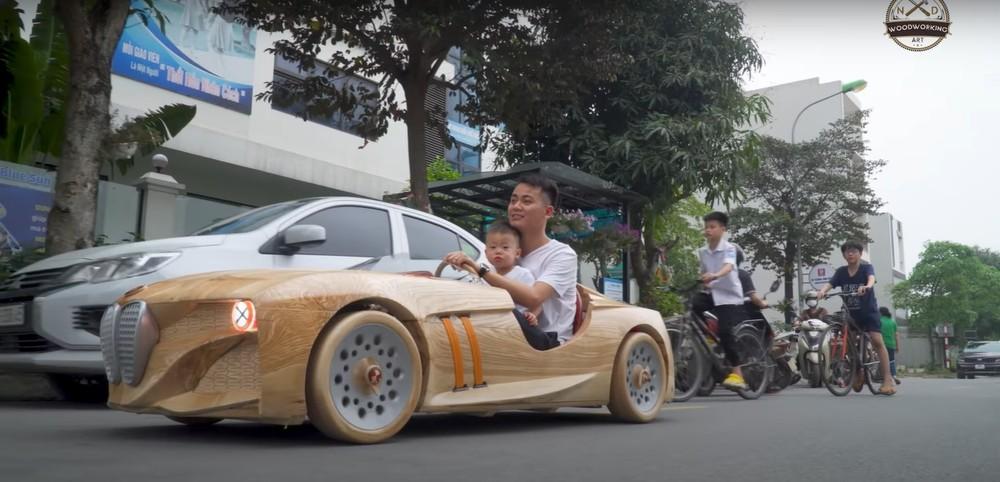 Anh Đạo điều khiển chiếc ô tô bằng gỗ đưa con đi mẫu giáo