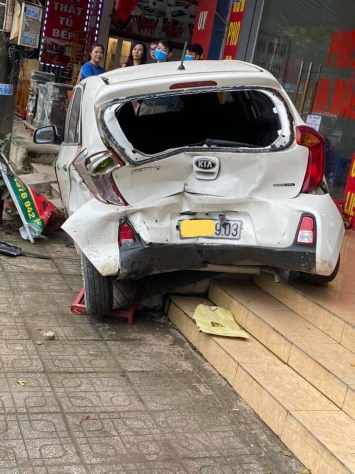 Chiếc Kia Morning nằm trên vỉa hè và bị hư hỏng khá nặng