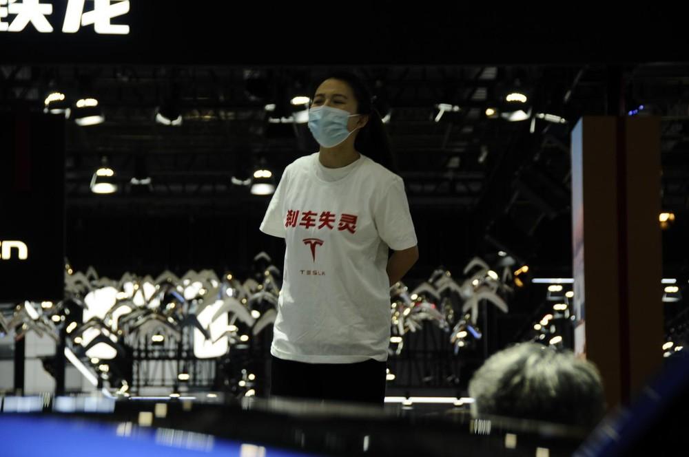Người phụ nữ mặc áo phông in dòng chữ Phanh mất kiểm soát và logo của hãng Tesla