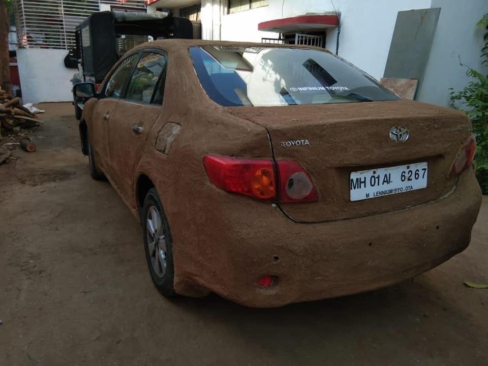 Bất chấp mùi khó chịu, người phụ nữ vẫn trét phân bò xung quanh chiếc Toyota Corolla Altis