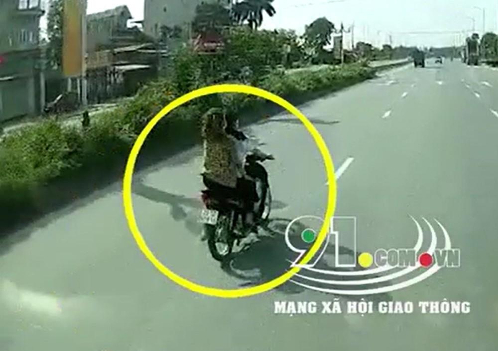 Hai cô gái không đội mũ bảo hiểm, đi xe máy trên đường trục chính của Khu công nghiệp Bắc Thăng Long