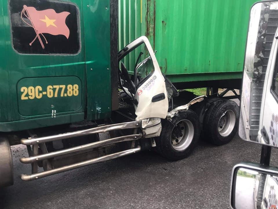Cưa bên ghế lái của chiếc ô tô tải mắc kẹt trên xe container