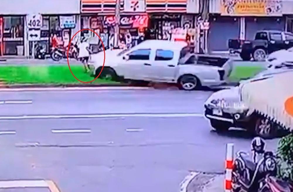 Người phụ nữ đi bộ nhanh chân bỏ chạy khi 2 chiếc ô tô lao về phía dải phân cách