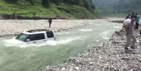 Người đàn ông đi lại trên bờ sông trong khi chiếc Land Rover bị ngập đến kính chắn gió
