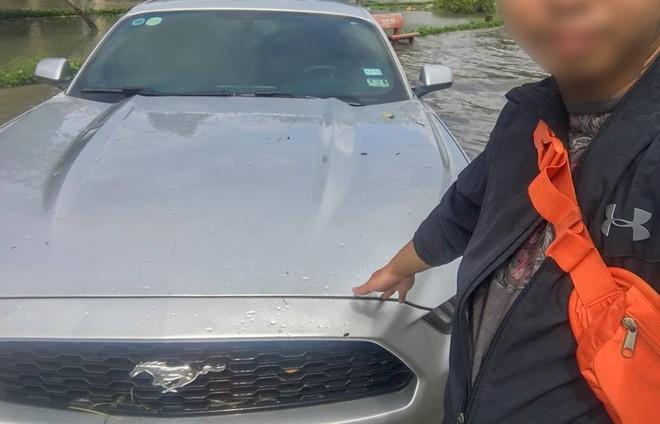 Người đàn ôngtự sướng cùng chiếc xe Ford Mustang màu xám bên dòng nước lũ đen ngòm