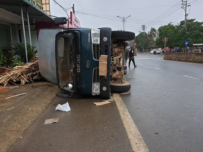 Chiếc ô tô tải chở gỗ lật bên lề đường