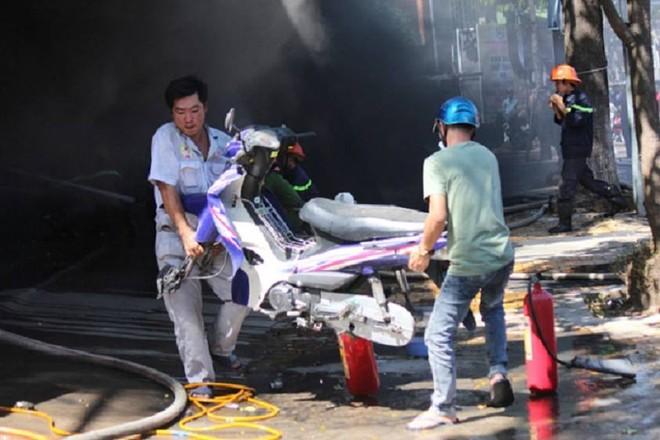 Một số người dân vận chuyển xe trong cửa hàng ra khỏi nơi cháy