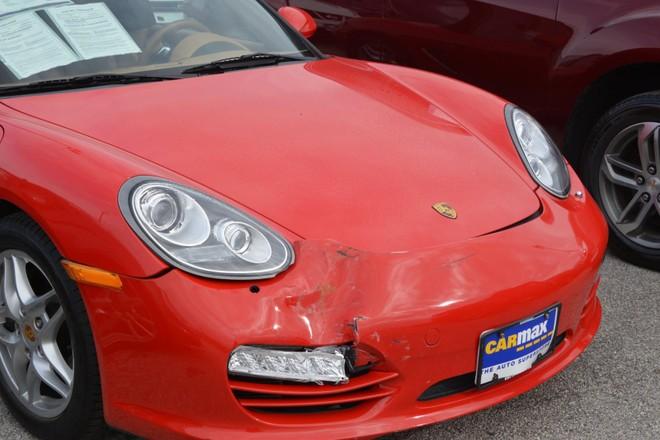 Chiếc xe thể thao Porsche màu đỏ bị biến dạng cản trước