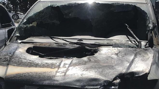 Một chiếc ô tô bị vỡ kính chắn gió và thủng nắp capô sau vụ cháy