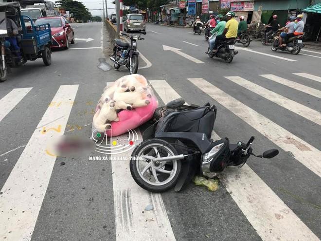 Chiếc xe máy vượt đèn đỏ nằm đổ trên vạch kẻ đường dành cho người đi bộ