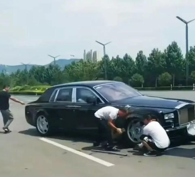 Hai người đàn ông xem xét thiệt hại của chiếc Rolls-Royce Phantom