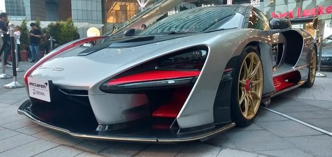 Chiếc McLaren Senna này có màu bạc đi kèm sợi carbon, các hoạ tiết đỏ cam và bộ mâm vàng đồng
