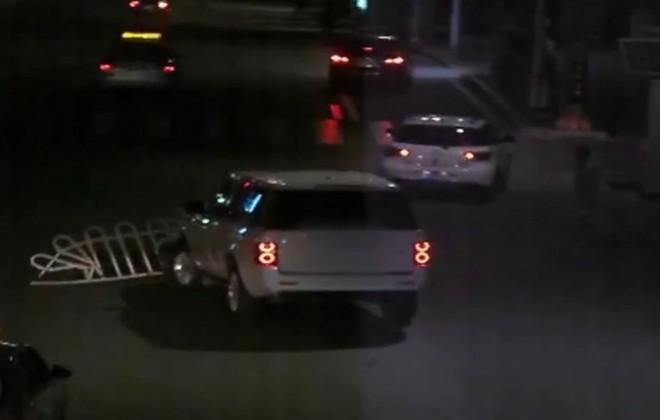 Chiếc Range Rover chạy trên đường với dải phân cách bằng sắt mắc ở đầu xe